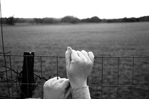 Hands clinging to a fence.
