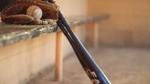 baseball glove and bat in a dugout