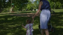 a mother pushing a stroller and holding her toddler daughter's hand walking in a park