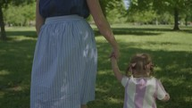 a mother and toddler girl walking in a park holding hands