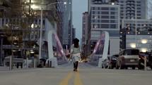 a woman walking across a city bridge