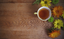 a cup of tea on table with bright flowers