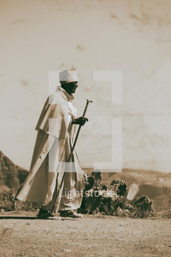 priest walking across a desert