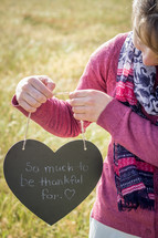 a child holding a sign that reads so much to be thankful for