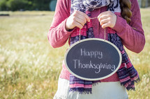 a girl holding a sign with the words Happy Thanksgiving