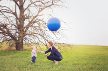 a mother and toddler boy with a balloon outdoors