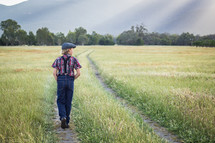 a young man walking in a field