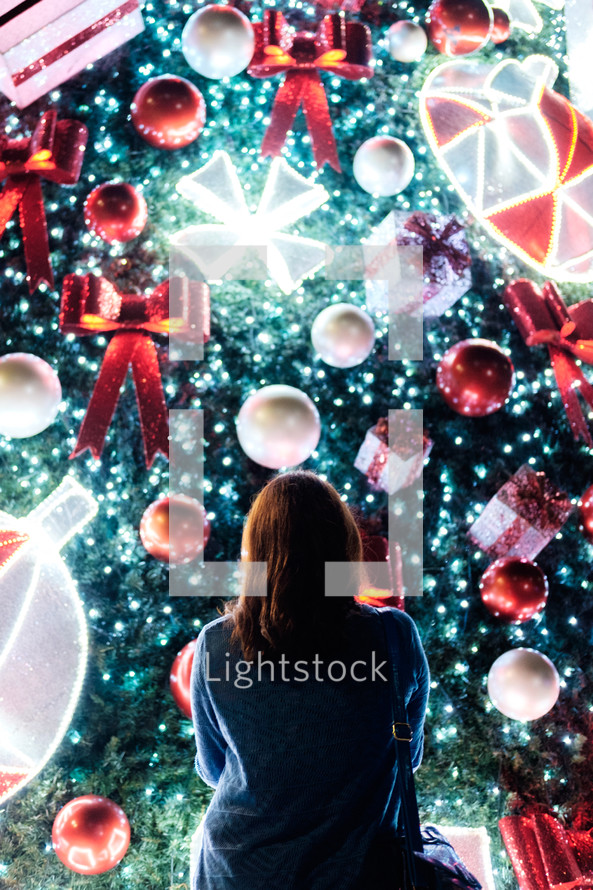 a woman looking at a Christmas light display