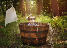 a boy sitting in a barrel holding a fishing pole in a forest