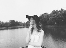 a woman in a sunhat standing by a lake