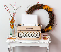 blank paper in a typewriter and fall decorations