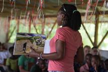 teacher instructing children in a school house