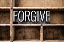 word forgive in blocks on a bookshelf