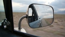 view out a car window and rear view mirror driving through the desert