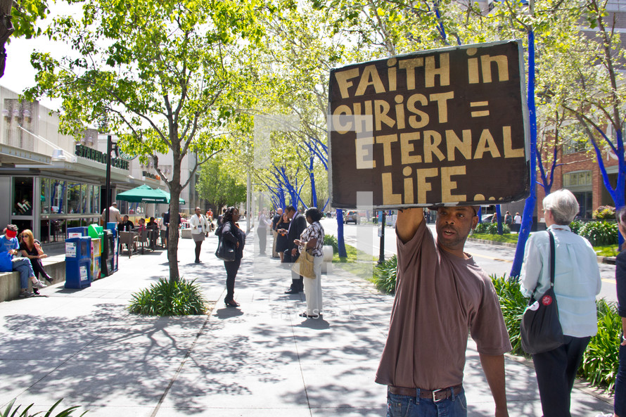 man holding a sign faith in christ equals eternal life