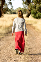 Girl Walking Down Dirt Road
