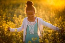a little girl walking through a field of yellow flowers
