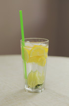 lemons and lime in water with a straw