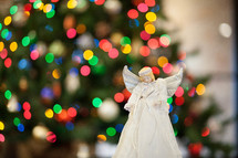 angel in front of a Christmas tree