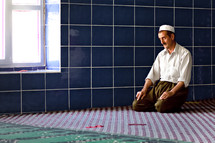 Kurd, Kurdish, Turk, Turkish, man performing Namaz, ritual Islamic prayer, traditional prayer cap, Mulsim man at Mosque. Southeast Turkey