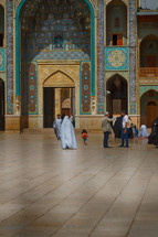 people walking through a courtyard in front of a mosque
