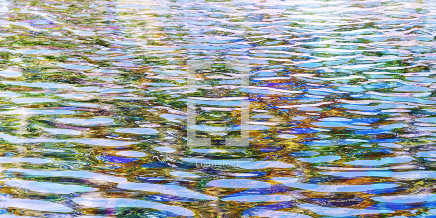 rainbow reflection glistening off of water surface