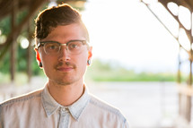 face of a man with ear gauges and glasses