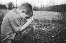 boy child with head bowed in prayer