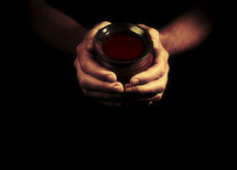 Hands offering a cup of wine isolated on black