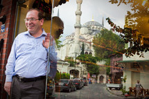 Shop owner with Blue Mosque in window reflection