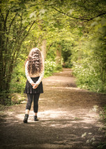 a teen girl walking down a path