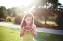 a girl child eating a watermelon outdoors