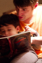 a father reading a Christmas story to his son
