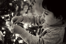a boy child decorating a Christmas tree