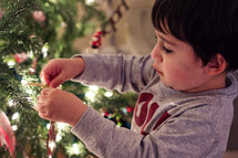 boy child decorating a Christmas tree