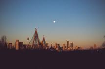 moon over a bridge in a city