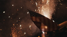 fireworks on the ground at night and American flag