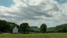 Timelapse of cloud movement over a mountain range, trees, and a white country church in a field of grass.