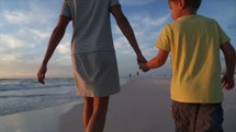 mother and son walking on a beach