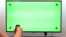 Woman hand with TV remote switching channels on a green screen TV