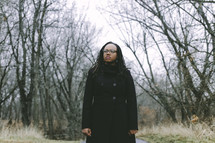 woman in a long trench coat standing in the woods