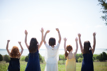 Girls standing outside with their arms raised.