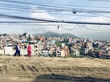 women walking on a dirt road through a poor city