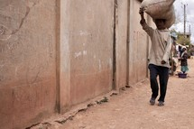 man walking carrying a bag of rice on his head