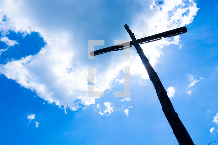 wooden cross silhouette against a blue sky