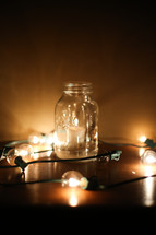 votive candle in a mason jar and a string of lights