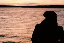 silhouette of a woman looking out at water at sunset