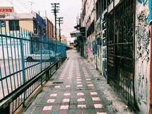 fence, gates, and graffiti on a city sidewalk
