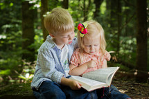 brother and sister reading a Bible together outdoors