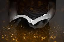 a man standing reading a Bible and glittery bokeh light